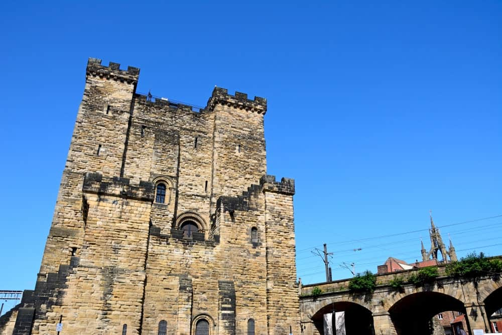 Square stone keep castle in downtown with a geometric roof.