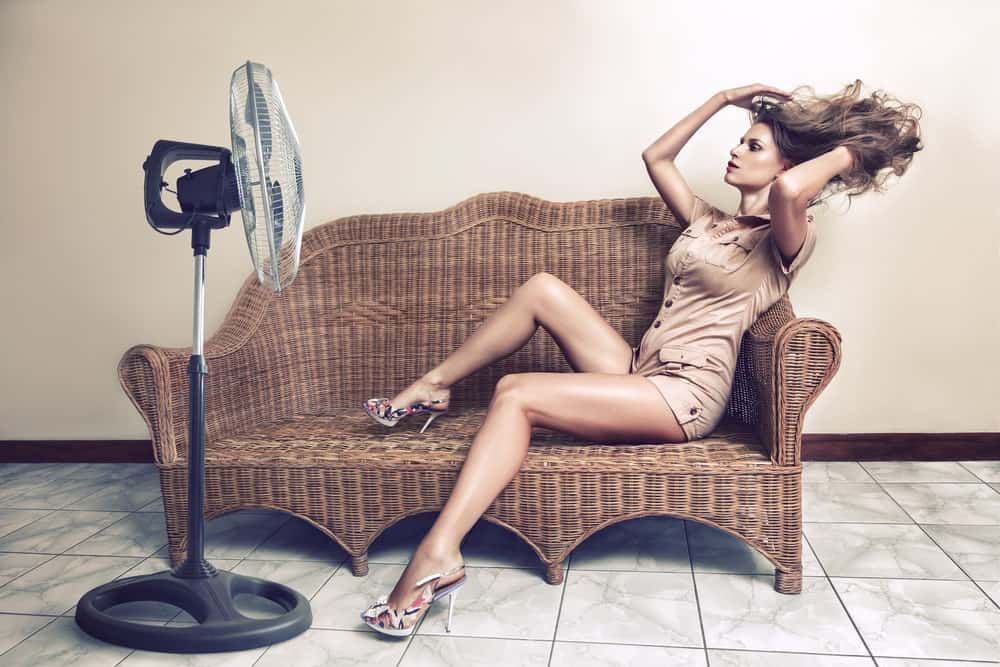 Woman sits on a wicker arm chair and keeps herself cool with a pedestal fan.