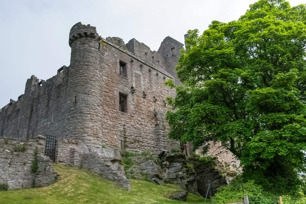 Stone keep castle with iron gate on a sloping grassland.