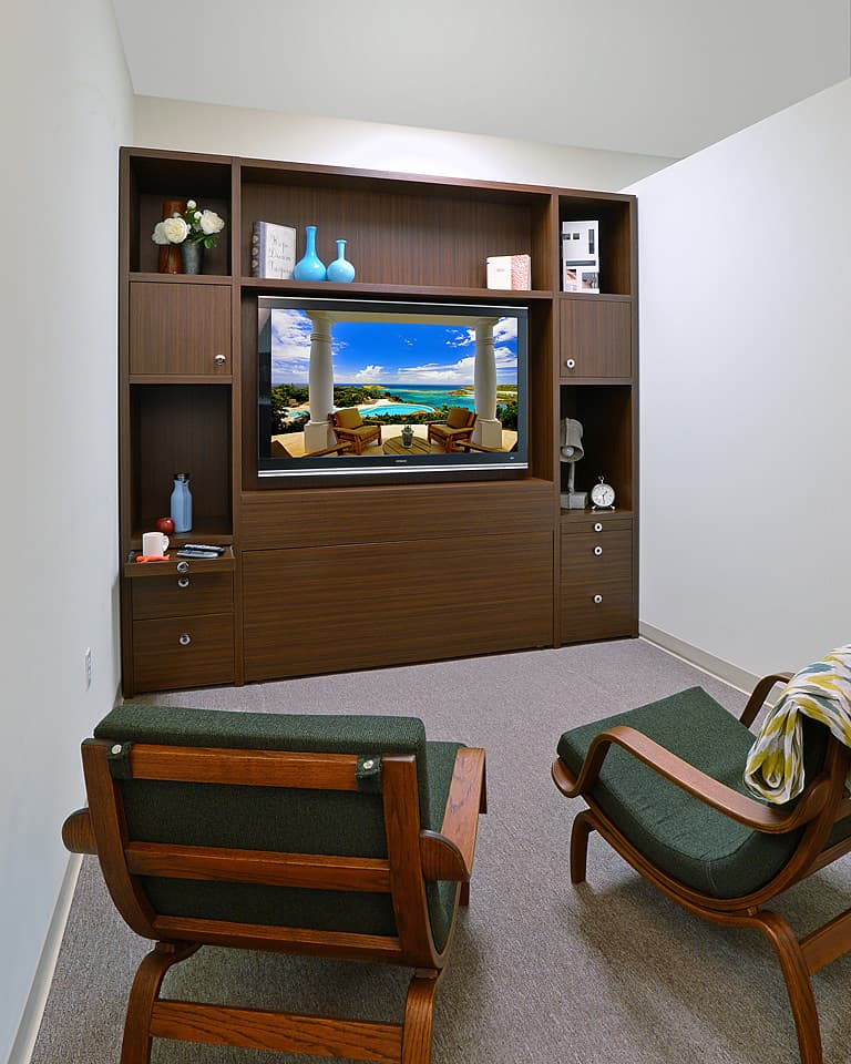 Modern wall bed as entertainment center with cabinets and open shelving in front of two armed chairs.