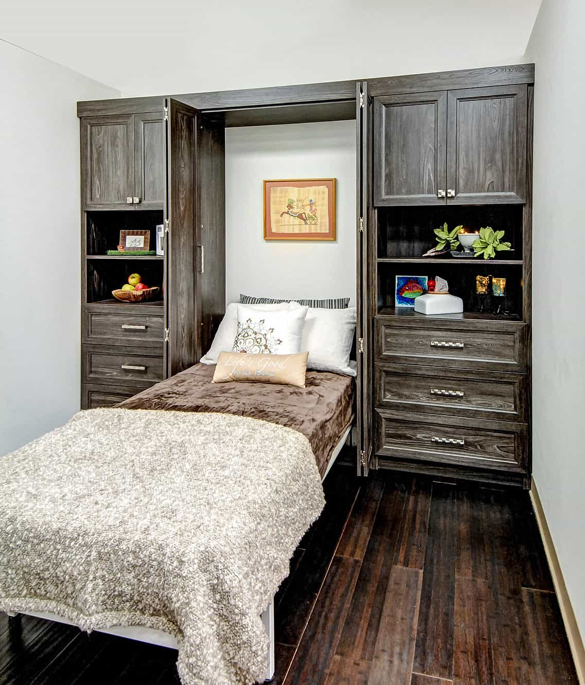 Wall bed under an overhead painting flanked by the wood double doors.