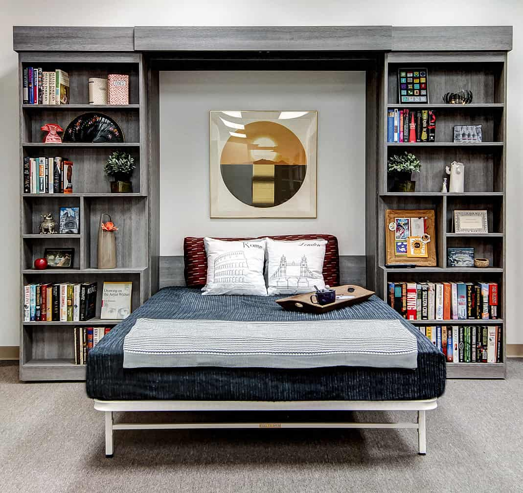 Beautiful wall bed with flanking floor-to-ceiling bookshelves by Closet Works.