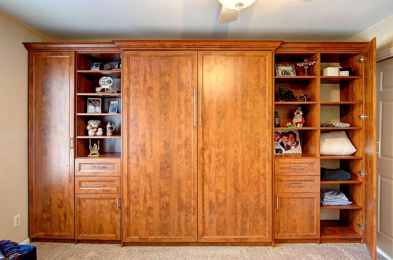Wall bed as floor-to-ceiling custom cabinetry made of medium-toned wood with flat cabinet doors and open shelving.
