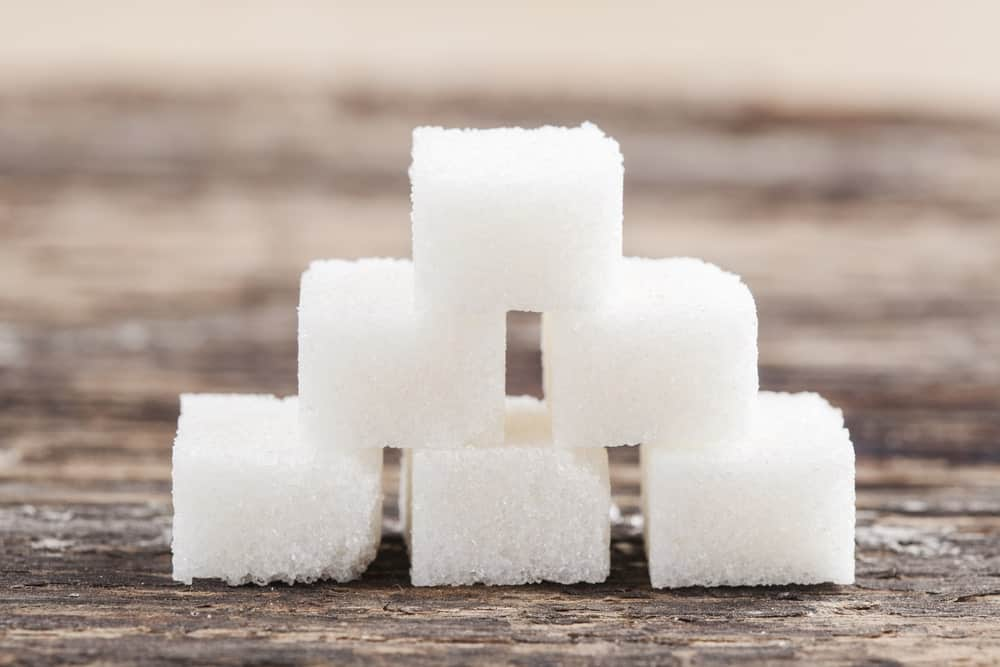 Pyramid stack of sugar cubes on wooden background.