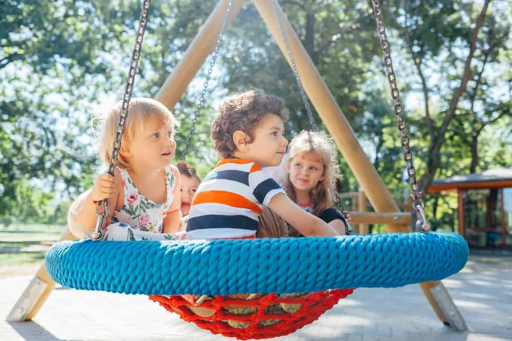Three playmates are sitting on a swing set at a park.
