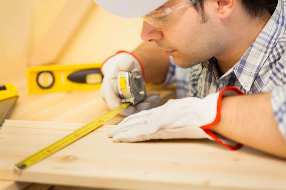 Worker using a tape measure on a piece of wood.