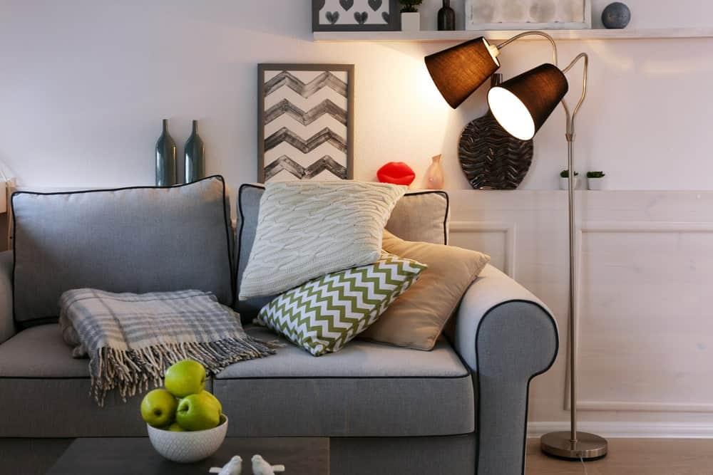 Floor lamp beside a sofa for task lighting.