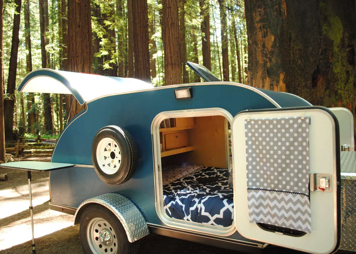 Side view of a teardrop trailer with open door and hatch. Table attaches to the side.