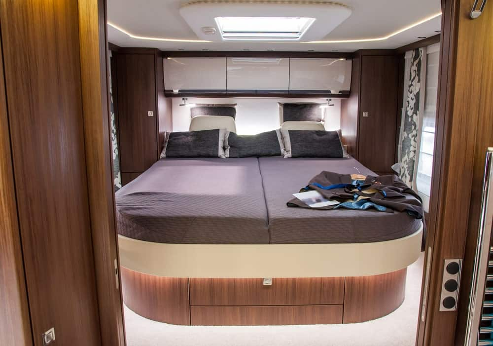Primary bedroom of a luxury RV trailer.