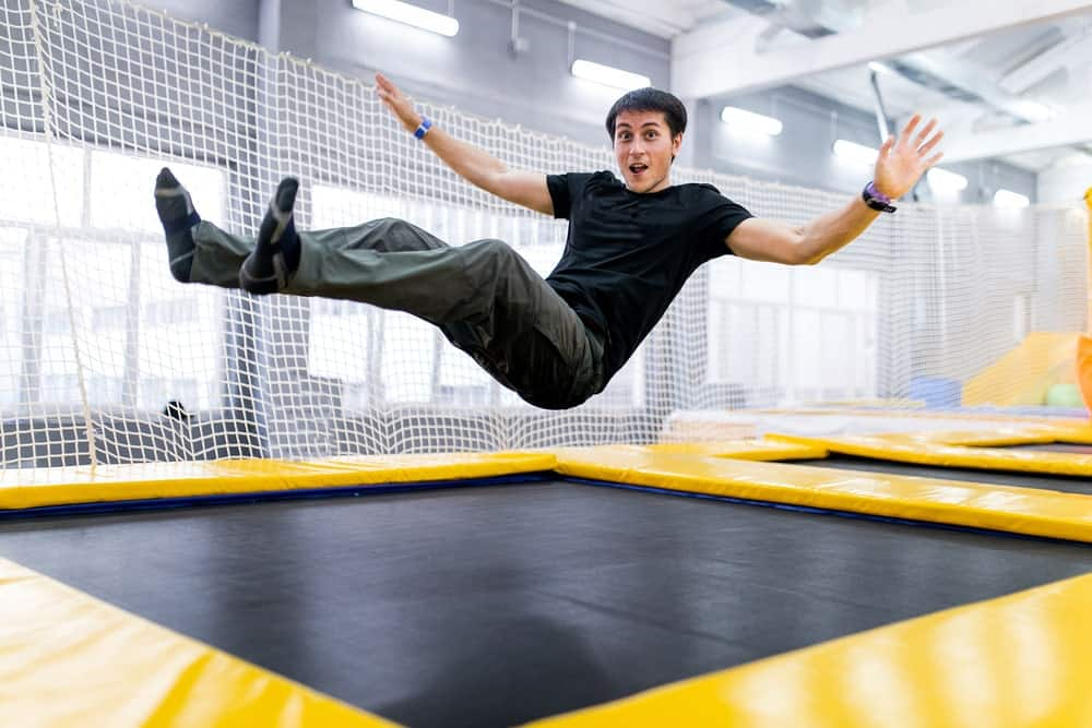 A guy is bouncing on a secured trampoline inside a fly park.
