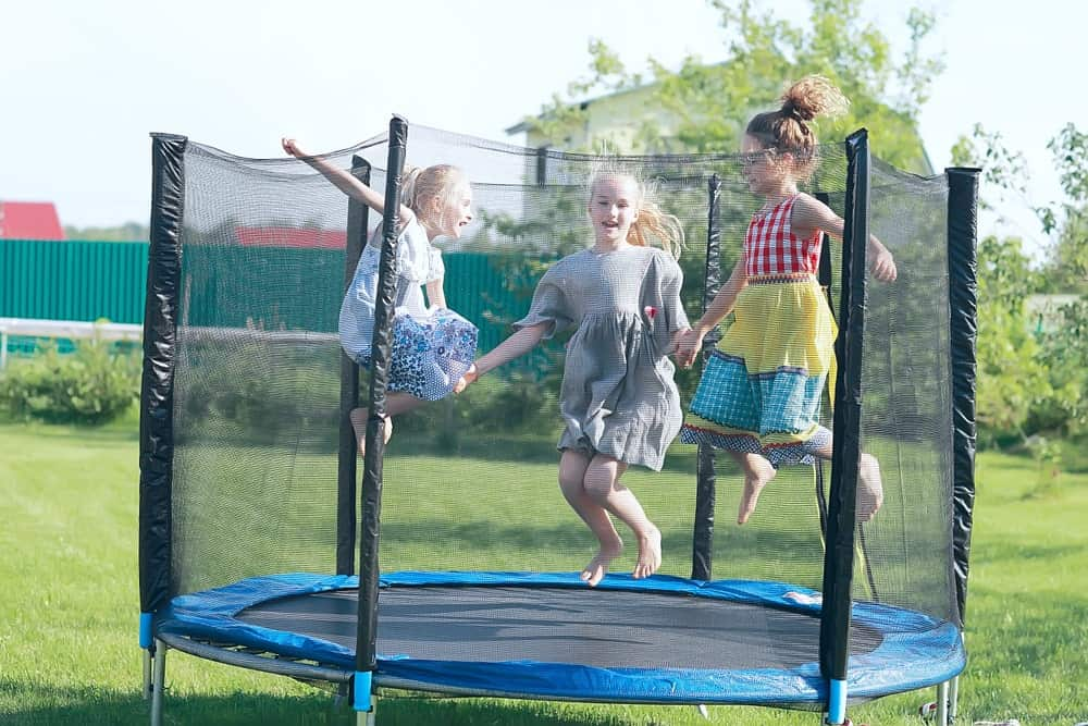 Three children are bouncing on a trampoline that's designed for children. This trampoline has a fence for safety.