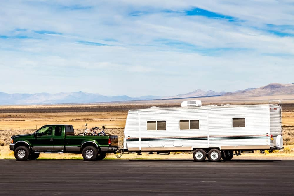Truck towing a travel trailer on the road.