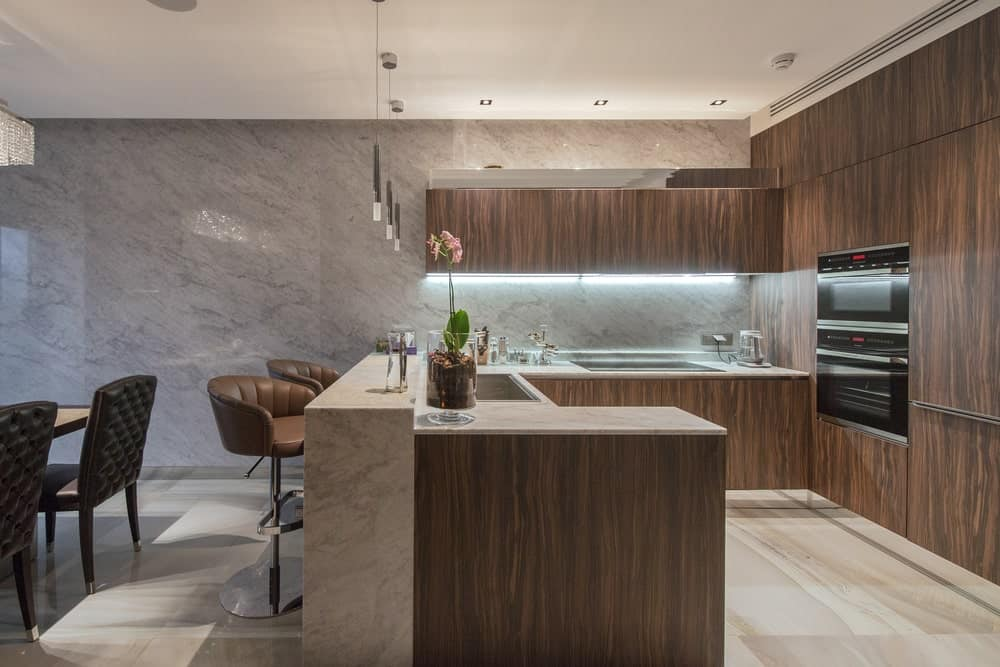 Eat-in kitchen with wood flat panel cabinetry, under-cabinet lighting, and peninsula breakfast bar.