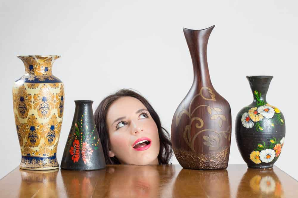 Lady admiring a variety of vases