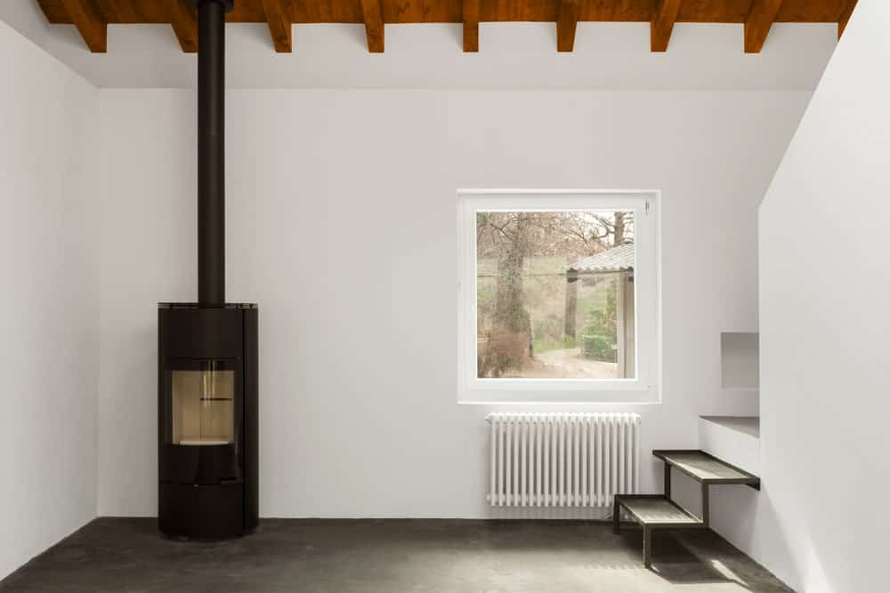 Pellet stove in a white modern room with beam ceiling and a square window.