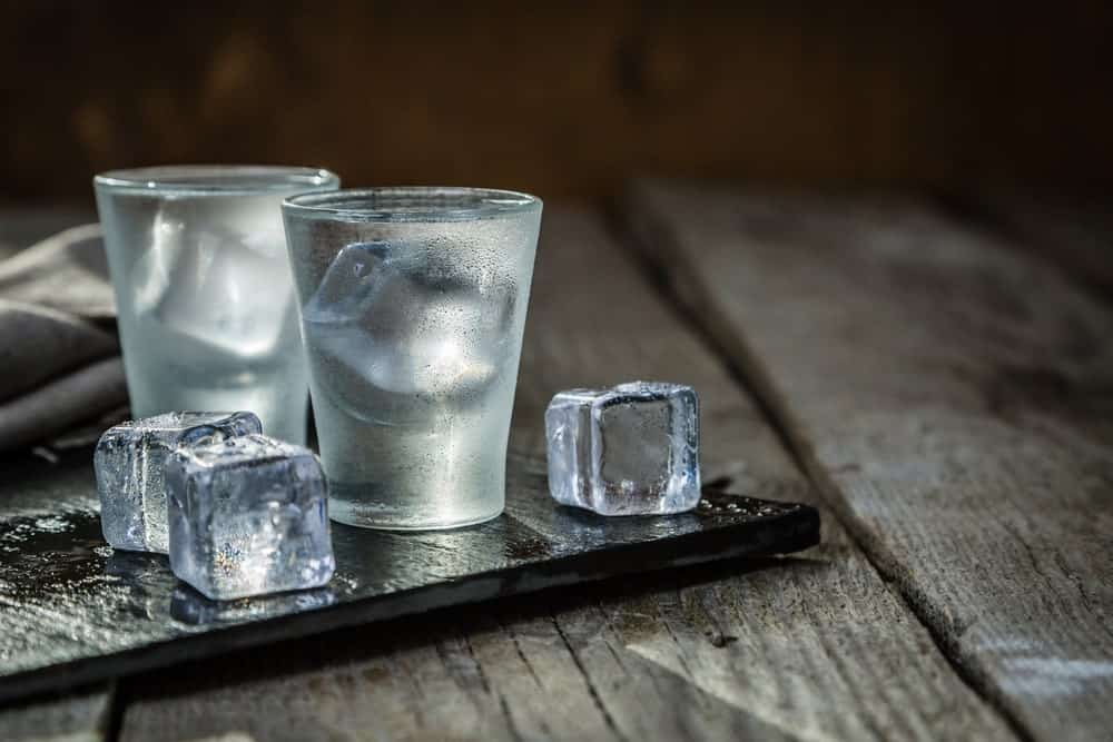 Vodka in two shot glasses beside ice cubes on rustic background.