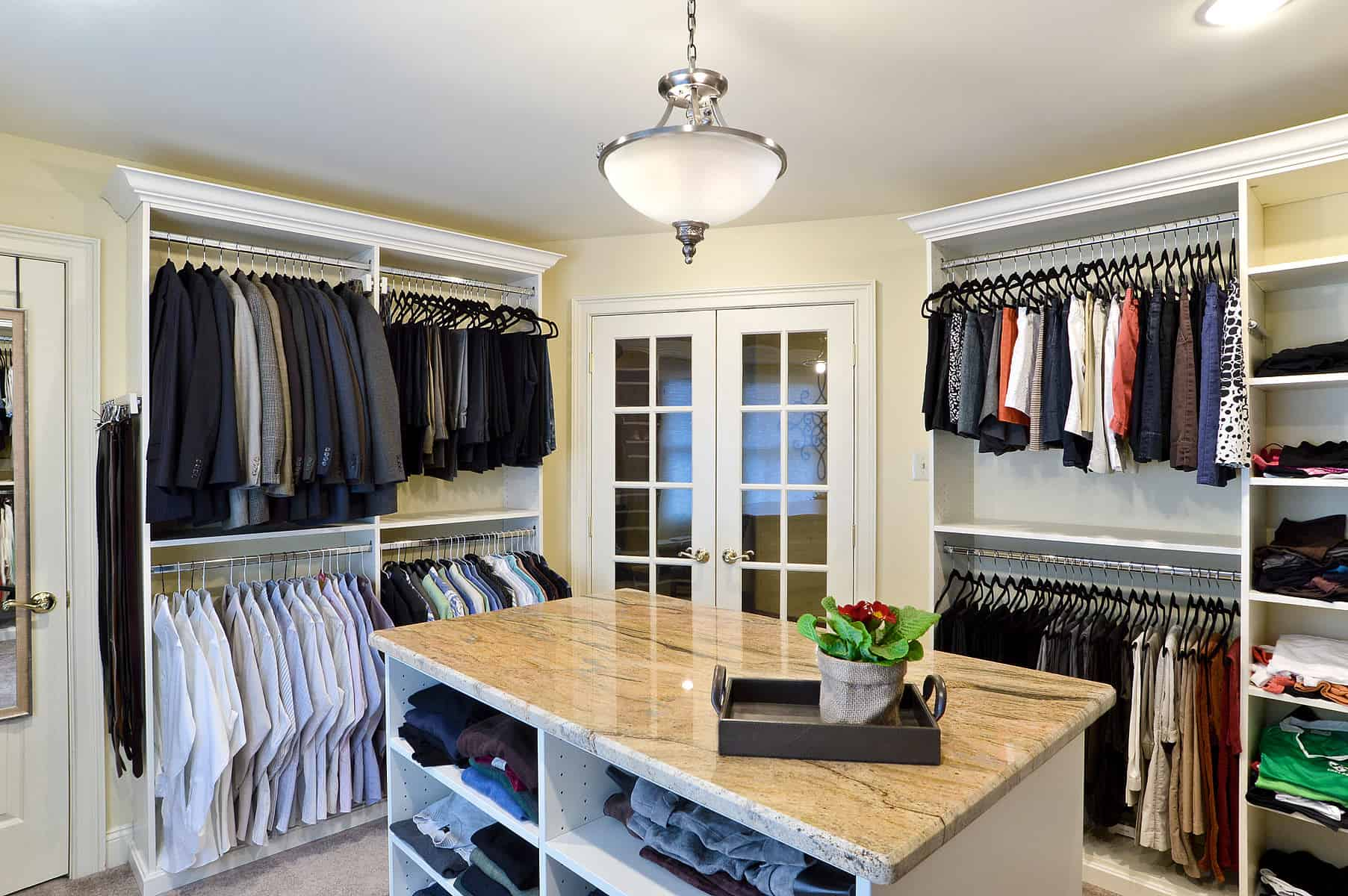 Large walk-in closet with open storage. French doors, and an island with open shelving for additional storage.