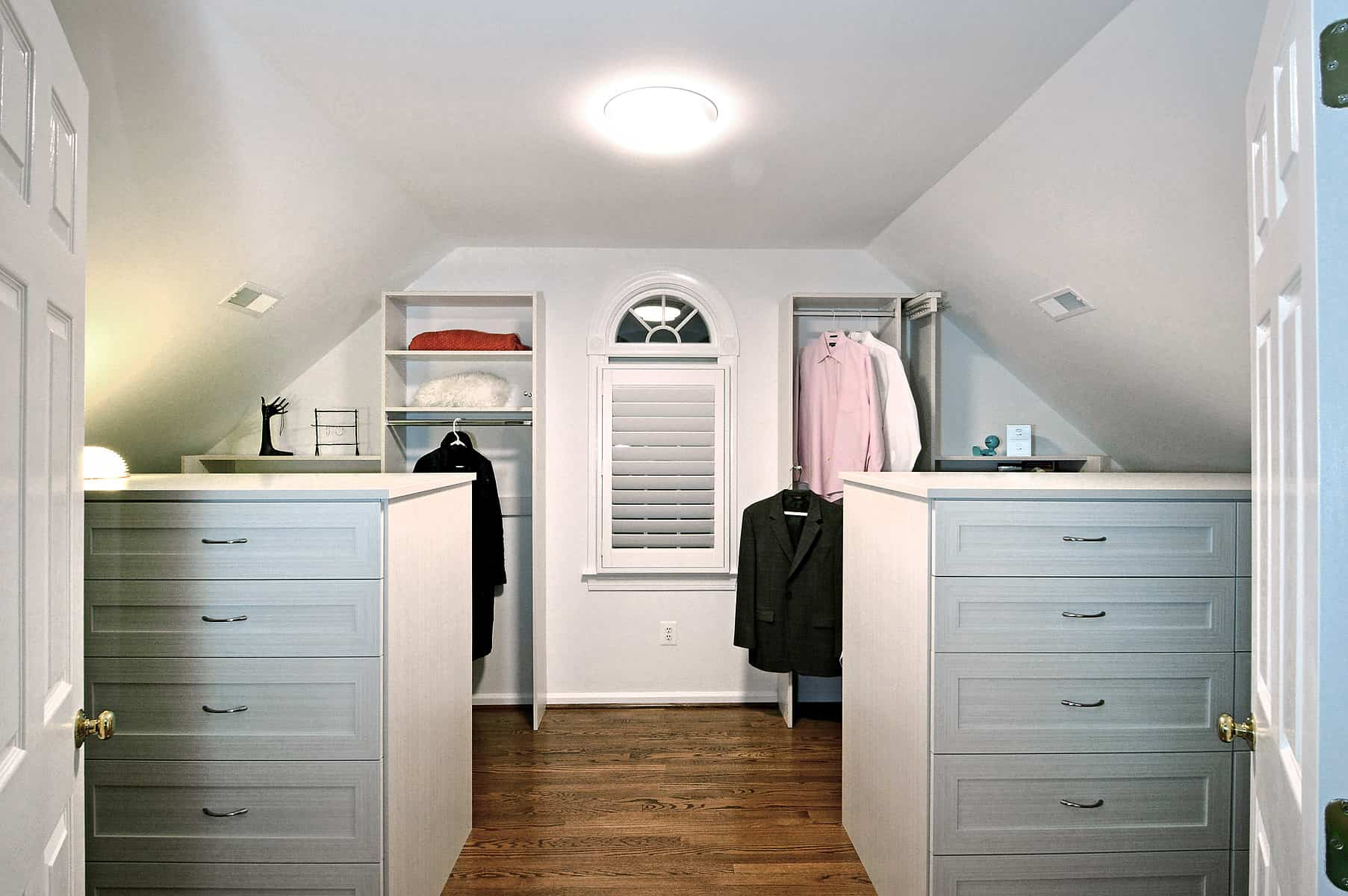 This bedroom closet features white walls and cabinetry, along with a hardwood flooring.