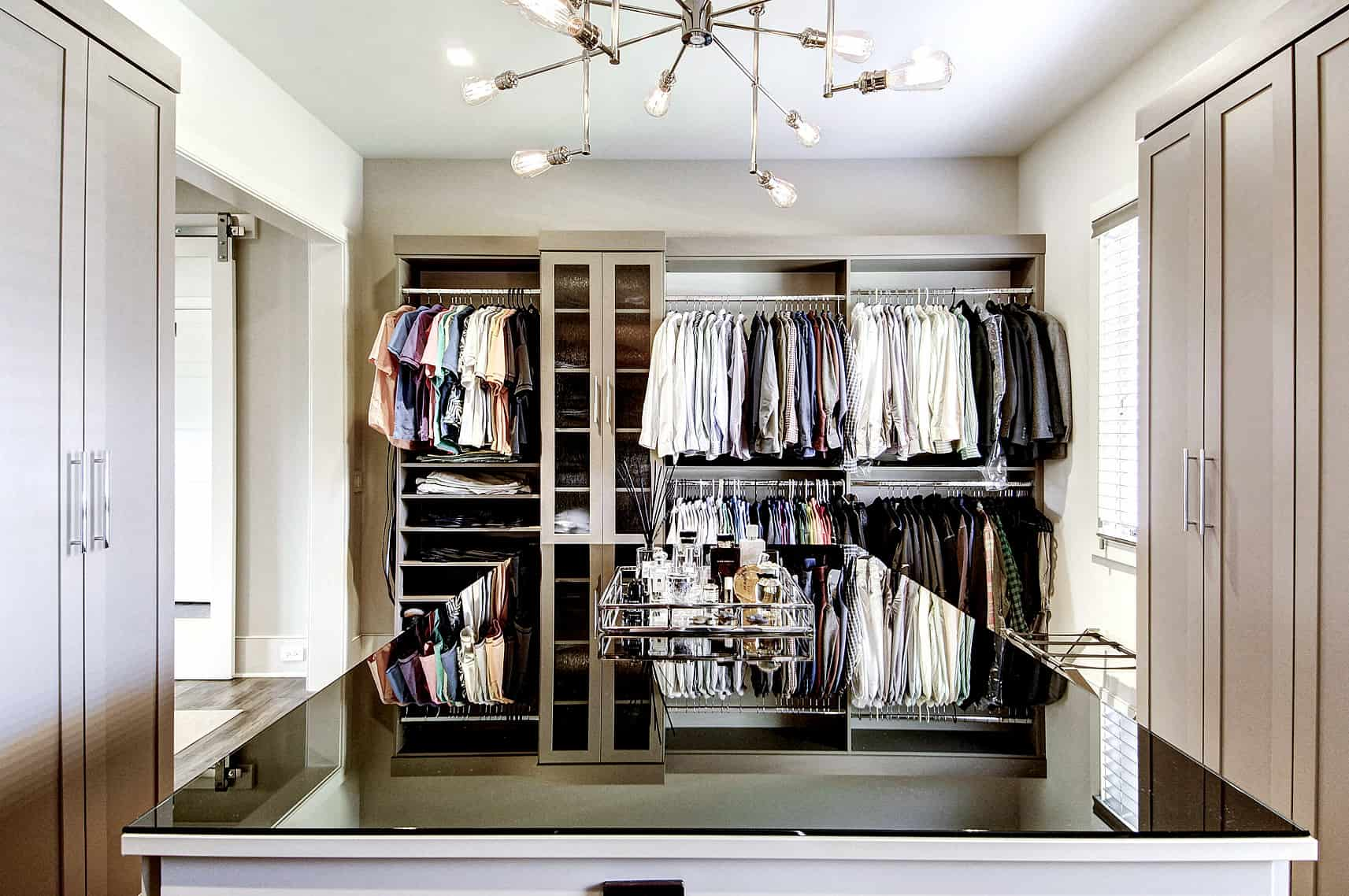 Closet with cabinets, open storage, and a large central island with dark glossy countertop.