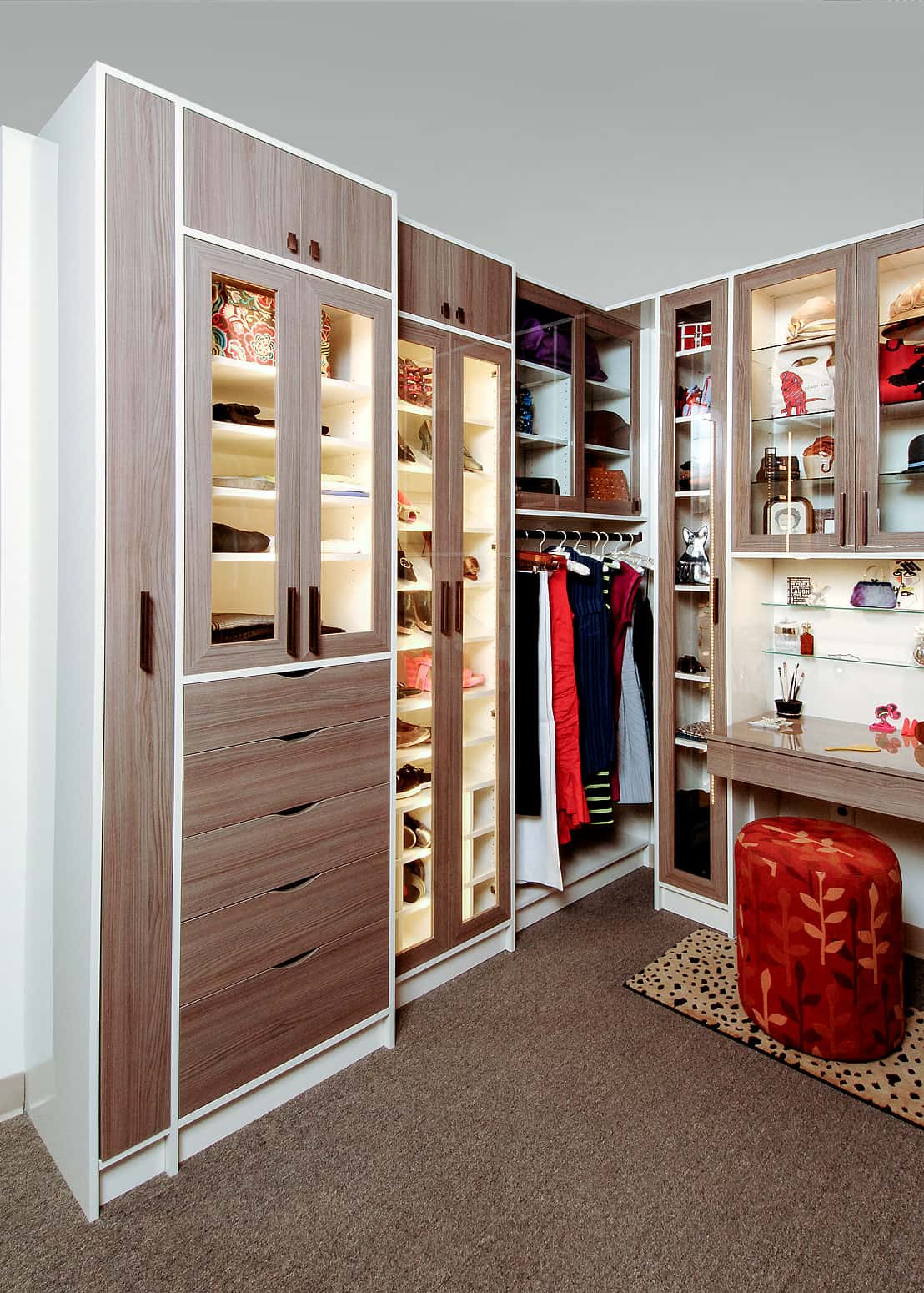 Custom closet with dresser and glass shelving.