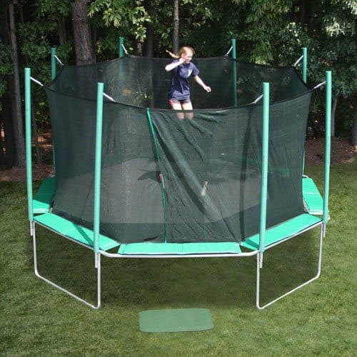 Girl is bouncing on her octagonal trampoline at her family's backyard.