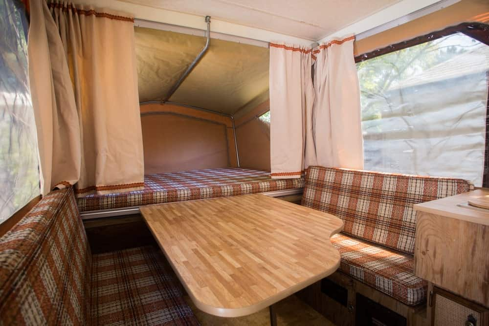 Curtains and mesh bug screen attached to the windows in the tent trailer dining nook.