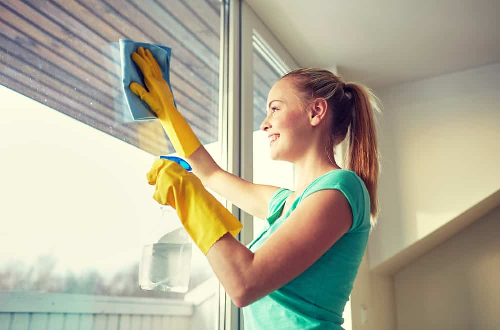 woman wearing rubber gloves cleaning windows