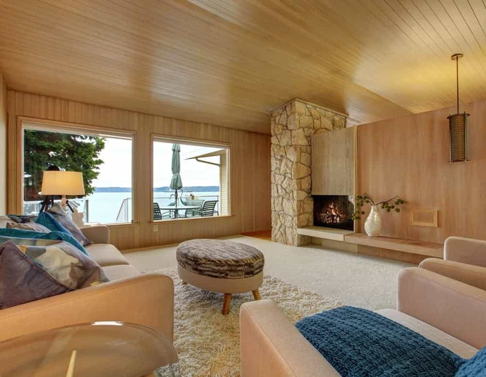 This is a beautiful house interior with wooden plank trim and fireplace. The comfortable couch, soft fur rug and ottoman create a romantic atmosphere.