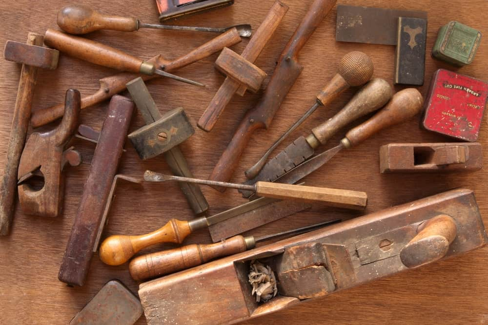Different types of vintage woodworking tools on wooden table such as spokeshave, chisel, screwdriver, hammer, etc.