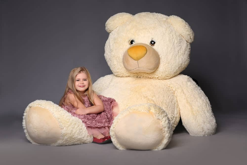 A young girl is posing with an extra large stuffed bear.