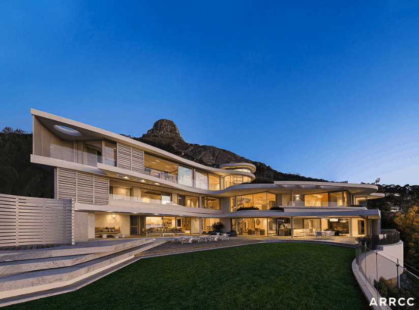 View of property and l-shaped mansion including grass area of mansion in South Africa on mountain.