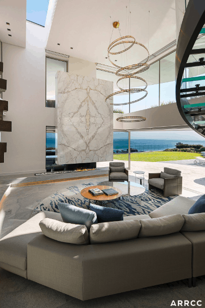 The thing that stands out most here is the statement spiraling chandelier. Using one or two modern pieces in your décor can add a contemporary twist to your living room even if the rest of your design is simple.