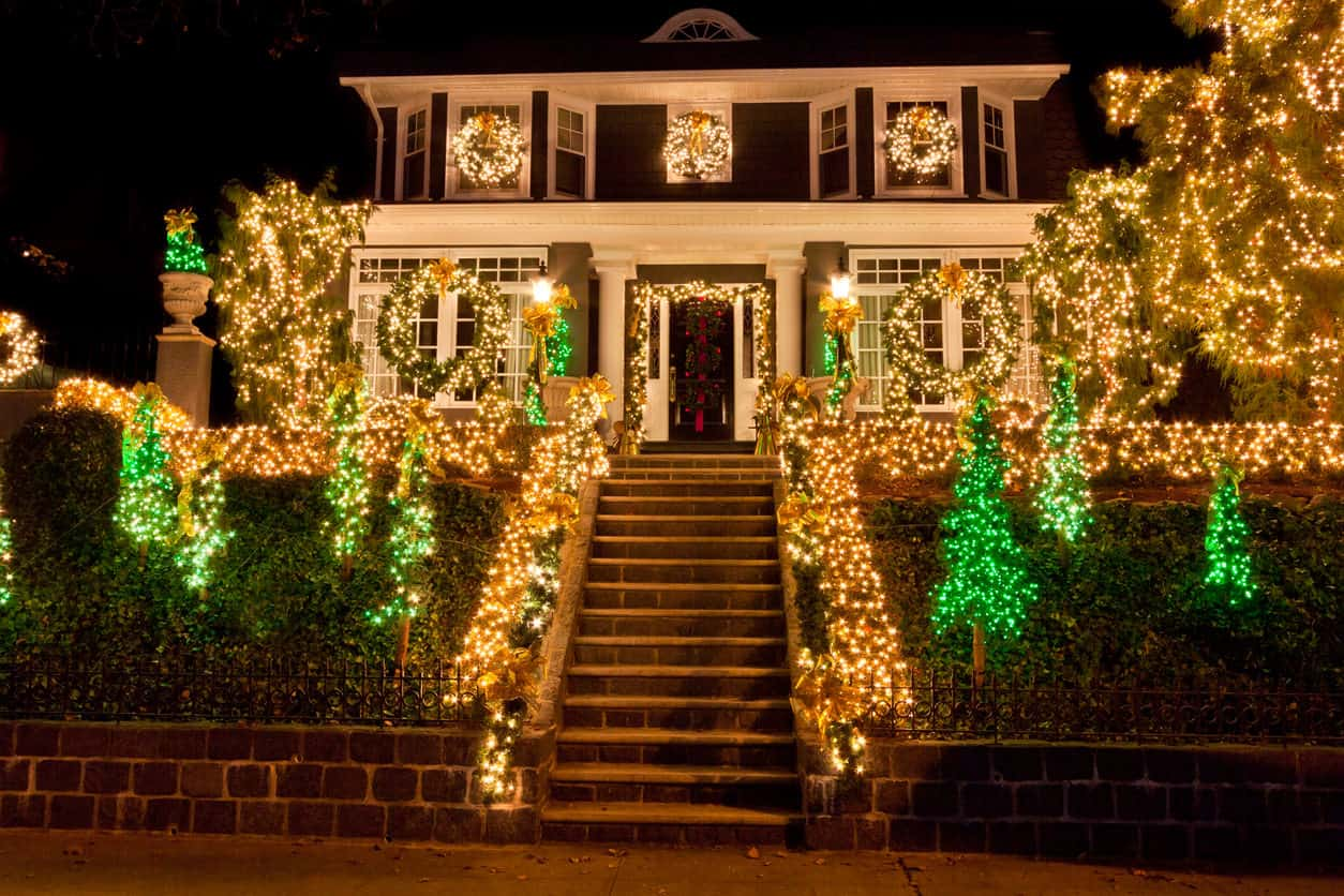 The sloping front yard offers plenty of great lighting opportunities here with the green light trees and white lights lining the railing along the stairs to the house which is nicely decorated with a series of wreaths.