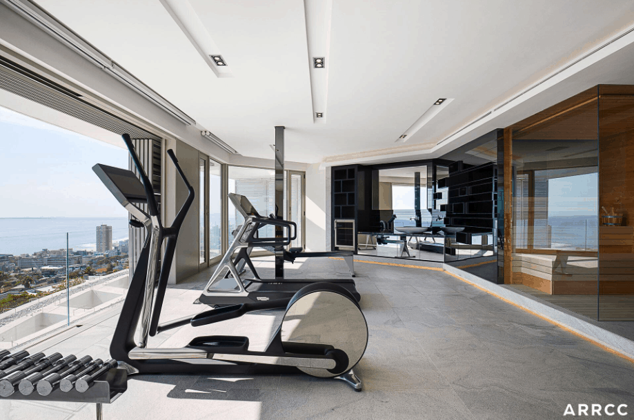 Home gym with dumbbells, elliptical trainer and treadmill on third story. Gym looks out over city and ocean. Sauna is off to the side of this gym.