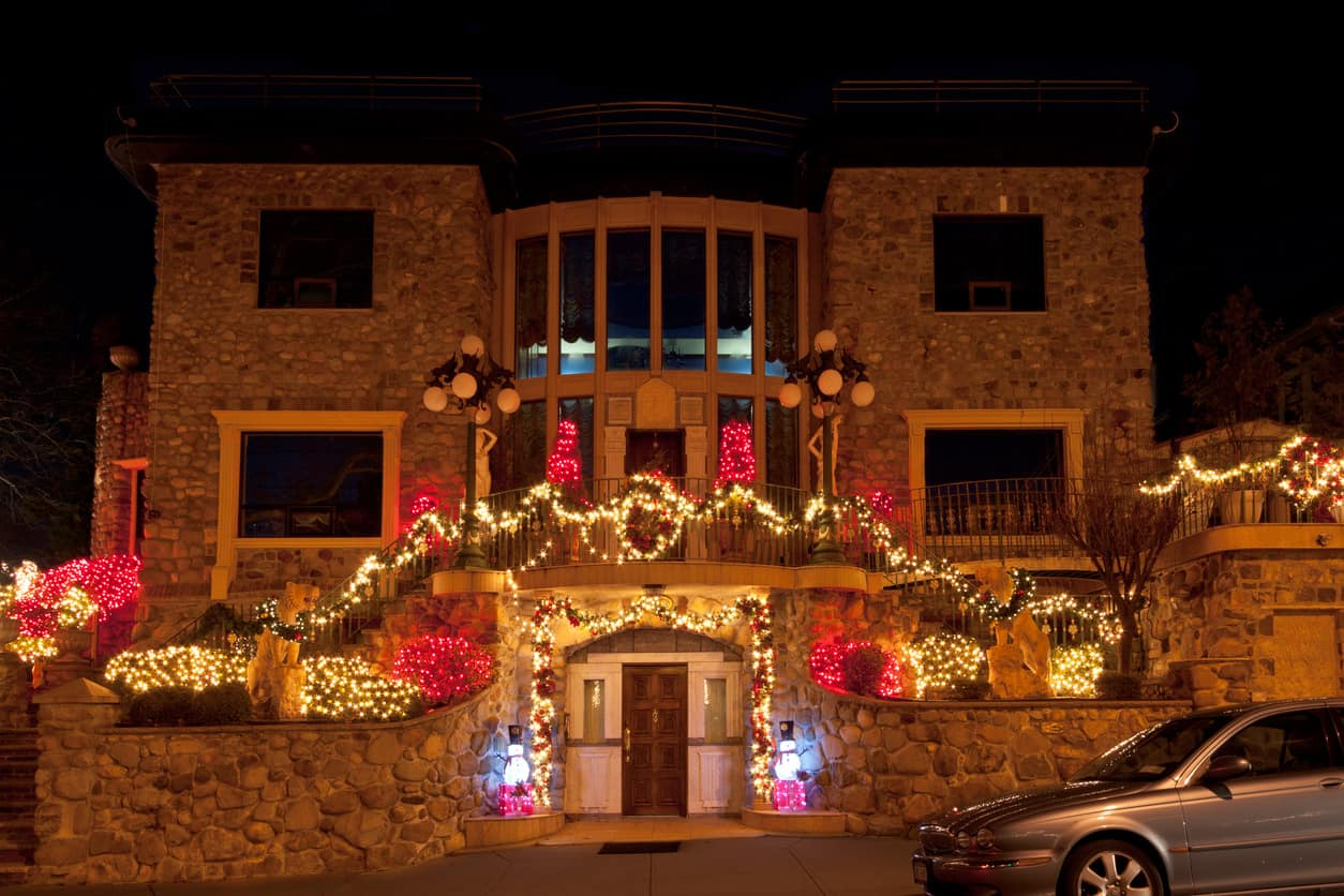 The front of this home has a large balcony with railing that is nicely lit up along with the gardens using only red and white lights.