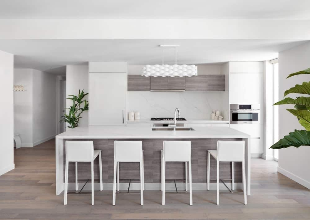 This is a bright and white kitchen with consistent bright white tones on its countertops that matches with the walls, stools and ceiling that hangs a decorative lighting over the kitchen island. These are then complemented by the wooden gray tones of the cabinetry and flooring.