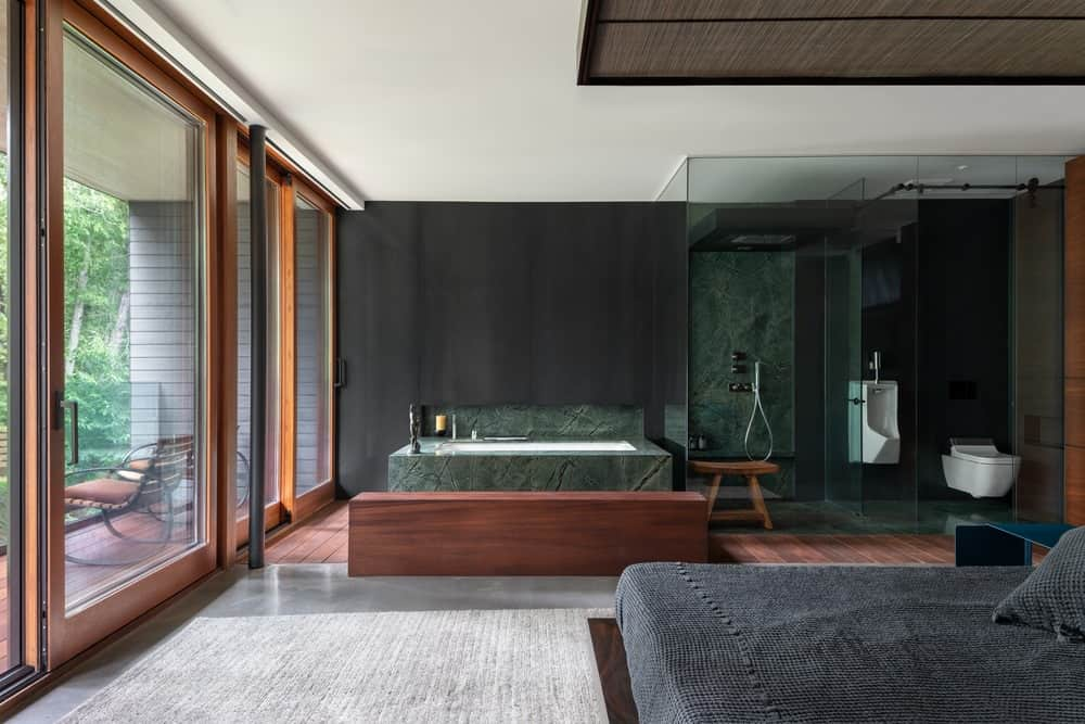 This primary bedroom design boasts dark tones of forest green. Talk about a modern makeover! One of the benefits of having the key to the primary bedroom is the bathroom suite. This open bathroom design is not an easy pill for traditional folks to swallow. But it gels with an individual who has a modern approach to living. The emerald marble used for the bathroom space and the dark wood paneling radiates a strong forest-like vibe. As a whole, you'll love this luxurious idea if you love taking long showers but hate the confined setting.