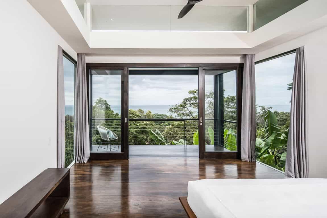Minimalist primary bedroom with private balcony.