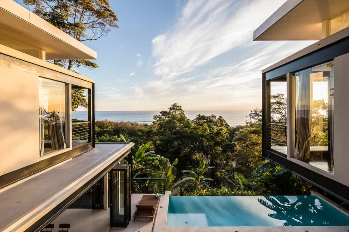 Small infinity plunge pool on edge of patio on hillside house overlooking jungle and the Pacific Ocean.