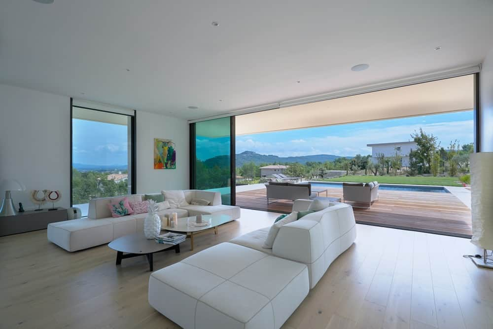 Large modern formal living room featuring white sofa set on top of the hardwood flooring. The sliding glass door leads to the home's pool-side deck.