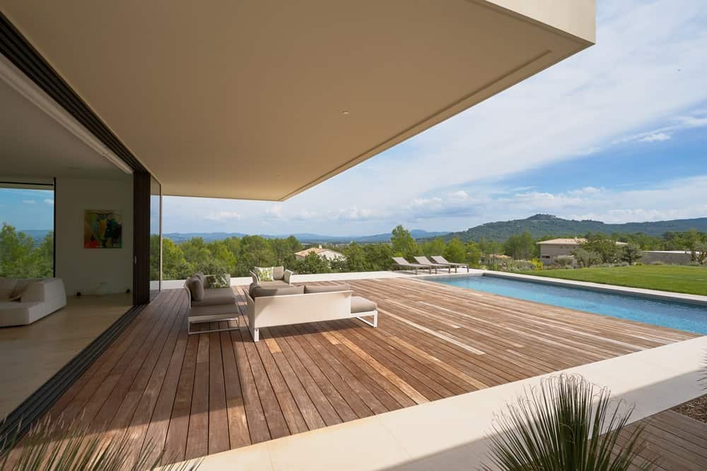 Large deck featuring a modish and comfortable sofa set overlooking the beautiful nature surrounding the home.