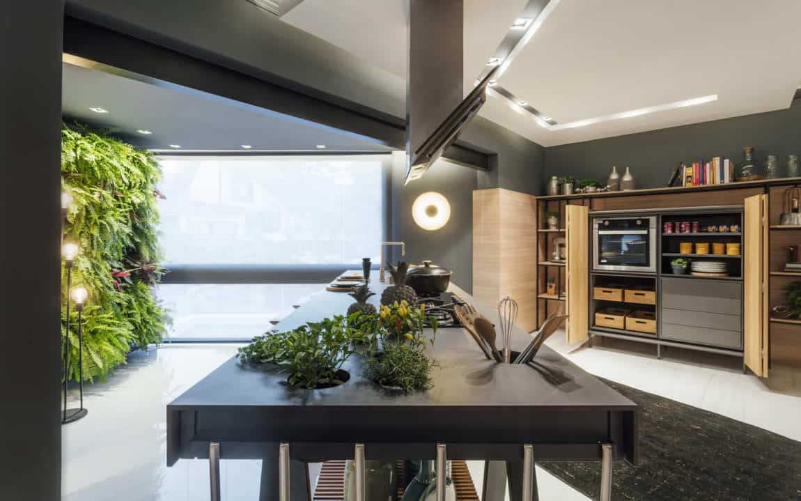 full view of the living wall with plants facing kitchen area.  The large window emits plenty of light into the industrial style, minimalist kitchen.  There is a wardrobe style cabinet that holds the island and some drawers but it's not the main storage function of this kitchen.