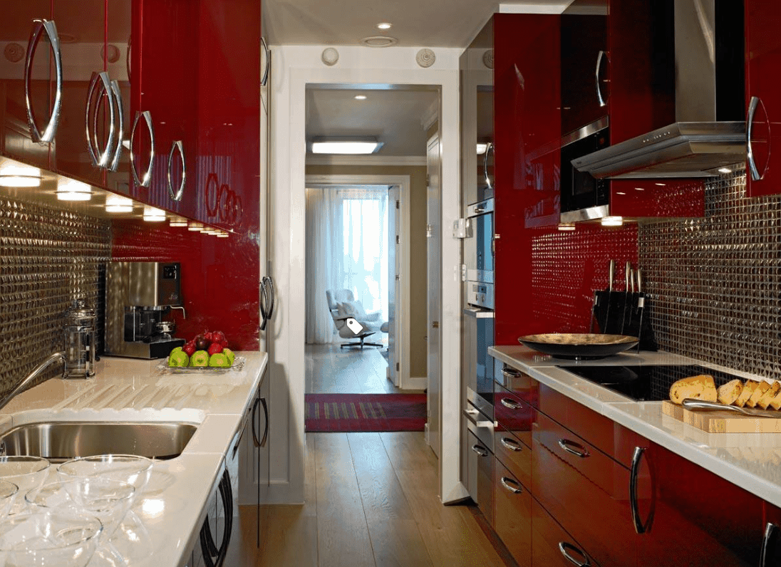 HIgh gloss deep red cabinets in a small galley kitchen with a fabulous chrome backsplash, chrome cabinet hardware and stainless steel appliances further offset with white countertops.