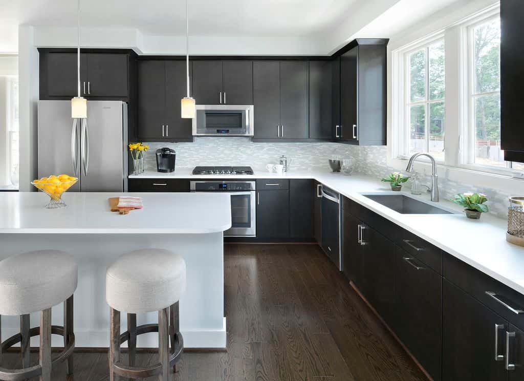 Black transitional kitchen design with contemporary black cabinets with stainless steel hardware along with stainless steel appliances and dark wood floor. I love the white countertops and all white island that contrasts the extensive use of black very nicely. This is one of the best black kitchen designs featured here.