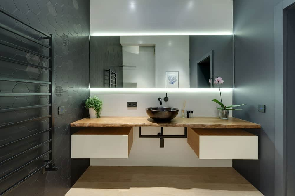 This powder room has a couple of black walls that give contrast to the hardwood flooring, wooden countertop of the floating vanity and the mirror above it that has lighting above and below.