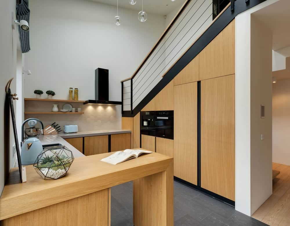 This is a small kitchen located beside the staircase with glass railings. You can see here that the kitchen has consistent wooden tones on its cabinetry and peninsula making the black tones of the appliances stand out.