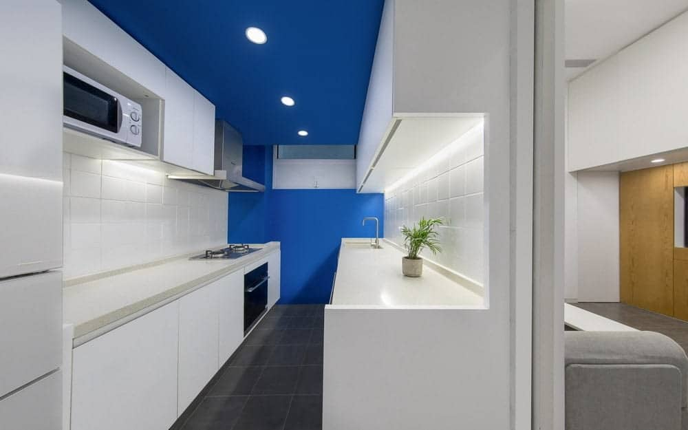 This is a narrow and small kitchen with modern and sleek white cabinetry on both sides paired with white counters and white backsplash to be contrasted by the royal blue tone of the far wall and the ceiling.