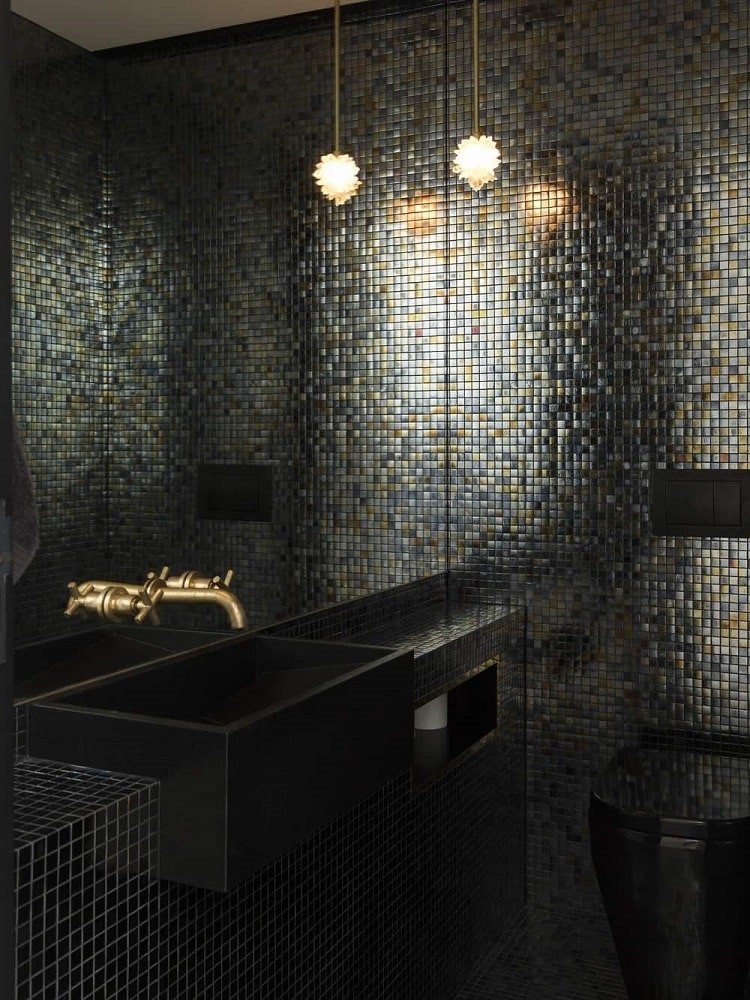 This is a black powder room that showcases the unique look of the dark wall tiles that go perfectly with the black sink and black toilet complemented by the large wall mirror.