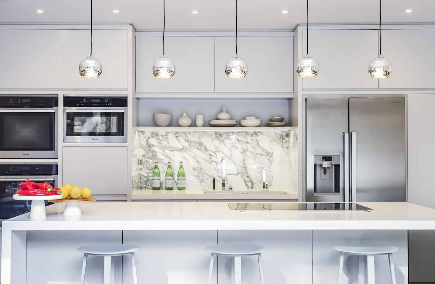 LLI Design put the new kitchen on the first floor. It's a modern white kitchen with an island. The marble backsplash is a nice touch. There is plenty of cabinet storage. Lighting is both recessed and pendant. I love this design.