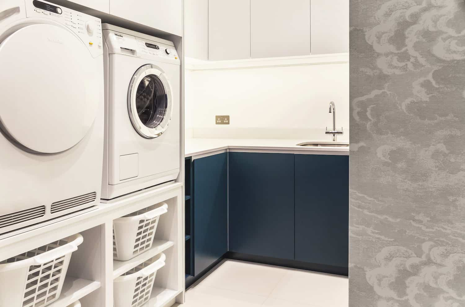 I love this bright, highly functional new laundry room with elevated washing machine and dryer with storage baskets underneath. There's counterspace, a sink and upper cabinets. This laundry room is more than adequate for a family.